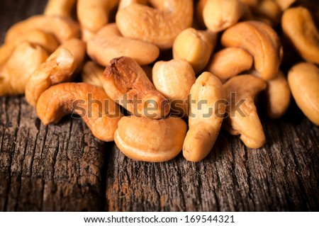 Close up to cashew nuts on the wooden table - stock photo
