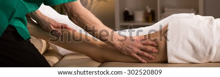 Close-up to man's hands massaging woman's thigh - stock photo
