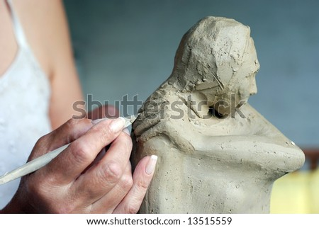 Close up to Sculptor's hand and her sculpture while she is working on it - stock photo