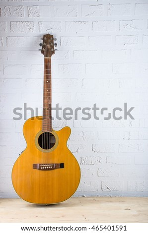 Close up to some of Acoustic guitar on white wall brick wall with space for Write message
