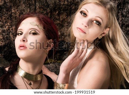 Close-up - together two beautiful makeup girls wearing an antique jewels, rocky wall on background - stock photo