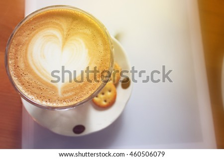Close up top of latte art on book and wooden table in cafe with selective focus concept