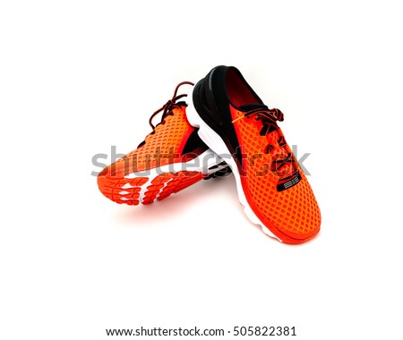 Close-up, top view a pair of brightly red running shoes isolated on white background. New unbranded running shoes, sneaker or training with clipping path and copy space. Active and healthy lifestyle.
