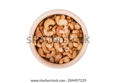 Close up top view of cashew nut in a wooden bowl, isolated on white background. - stock photo