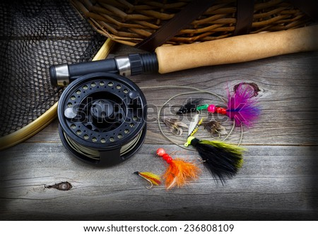 Close up top view of  fishing fly reel, landing net, creel and assorted flies, partial cork handled pole on rustic wooden boards with vignette border  - stock photo
