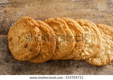 Close up Top View of Fresh Homemade Macadamia Cookies on Rustic Wooden Table - stock photo