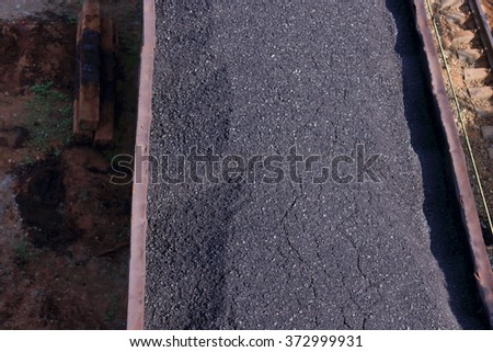 Close-up top view of wagon with coal and lying logs in summer sunny day - stock photo