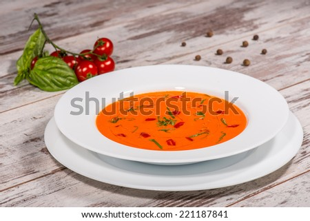 Close-up top-view picture of cold tasty tomato soup gazpacho with species on the wooden table in vegan caffee with tomatoes standing near a plate, with copy place  - stock photo