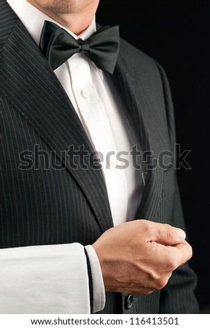 Close-up torso shot of a fine dining waiter in a bowtie and tux with a white pressed napkin over his arm. Side View. - stock photo