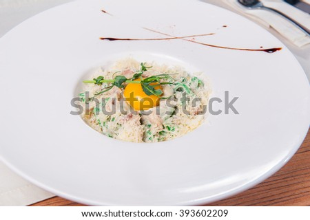 Close up Traditional Italian spahgetti Pasta Carbonara with roasted bacon,  and raw egg  and parmesan cheese sauce decorated with fresh herbs and on the white plate on the served restaurant table