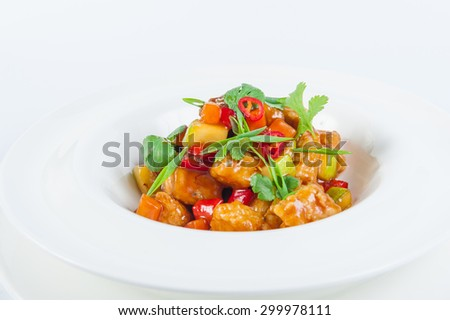 Close up Traditional Japanese dish of roast pork with vegetables in a sweet - sour sauce garnished with parsley in a round plate on a white background isolated