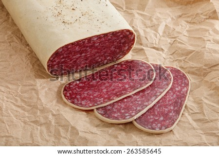 Close-up traditional sliced meat sausage salami on craft paper background. All in focus. - stock photo