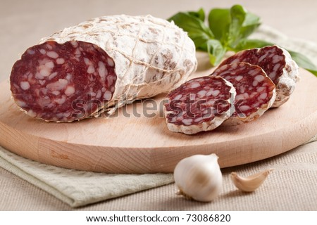 Close-up traditional sliced meat sausage salami on wooden board with head of garlic and green herbs on textile towel - stock photo