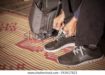 close up ,Traveler man hands tying shoelaces ,Backpacker man prepare travel in holiday ,vintage tone