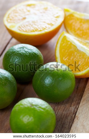 Close up tropic fruits orange and lime on the wood table