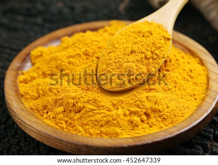 Close up Turmeric powder in a wooden bowl.