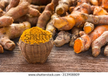 Close up turmeric powder on grunge wooden background.