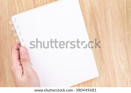 Close up Two Hand holding empty white open book above wood desk ,Mock up template for adding your content - stock photo