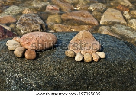 close up two trace feet made of a pebble stone on the sea wave backdrop  - stock photo
