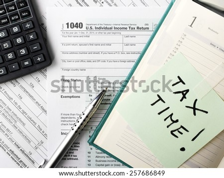Close up U.S. Individual tax form 1040 with calculator and pen. - stock photo