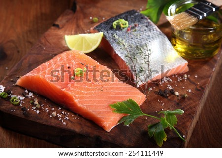 Close up Uncooked Fresh Salmon Fish Slices on Wooden Cutting Board with Herbs and Spices - stock photo