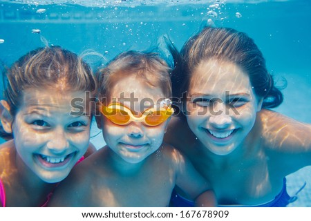 Close-up underwater portrait of the three cute smiling kids