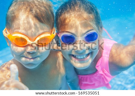 Close-up underwater portrait of the two cute smiling kids - stock photo