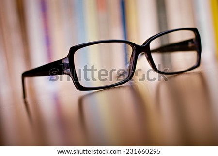 Close up Unisex Eyeglasses with Black Frame on Top of Wooden Table at the Office. - stock photo