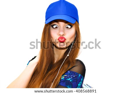 Close up urban colorful portrait of young hipster girl making crazy grimaces and duck face, gorgeous positive smile, bright makeup, long hairs, blue navy casual outfit, sportive cap, sending kiss. - stock photo