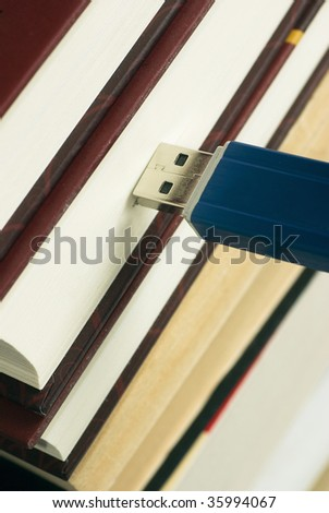 Close-up USB memory stick connected to books - stock photo