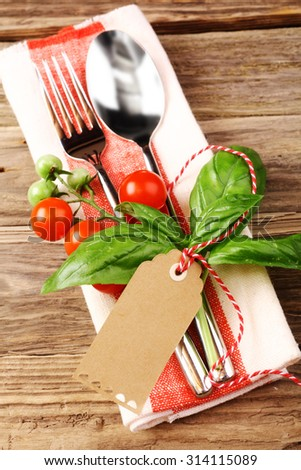 Close up Utensils on Napkin Styled with Tomatoes, Basil Leaves and Brown Tag with Copy Space, Placed on Top of Wooden Table. - stock photo