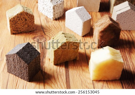 Close up Various Scattered Blocks of insulation Model Hous in Different Standing on Top of the Wooden Table - stock photo