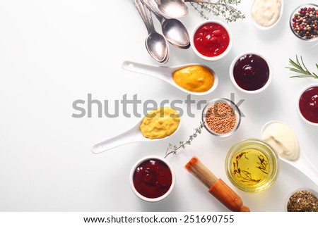 Close up Various Spicy Rubs and Marinades on White Table with Spoons and Brush, Emphasizing Copy Space. - stock photo