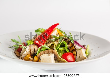 Close up Vegetarian salad with grilled vegetables, feta cheese, fresh tomatoes, lettuce and arugula decorated with walnuts and dried oregano on the white plate isolated on white background - stock photo