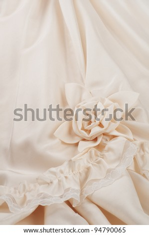 Close up Vertical of Off White Wedding Dress Details, including Ruffle, Lace, and Rolled Flower
