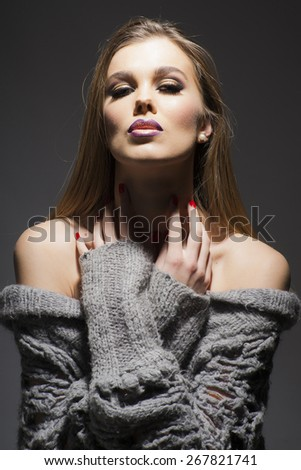 Close-up vertical portrait of beautiful woman wearing grey  clothes with make-up on the face looking at the camera - stock photo