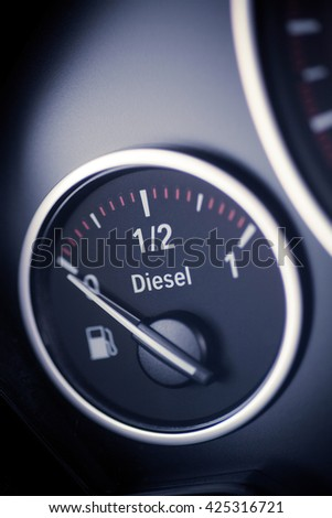 Close-up vertical shot of a diesel fuel gauge in a car. - stock photo