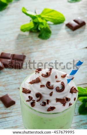 Close up vertical shot of the mint milkshake with blue straw and chocolate chips on its top. Leves of mint and pieces of chocolate on the blue table. Served natural drink. - stock photo