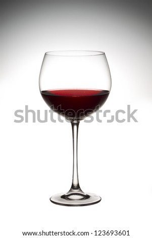 Close-up vertical shot of wine in wine glass against white background. - stock photo