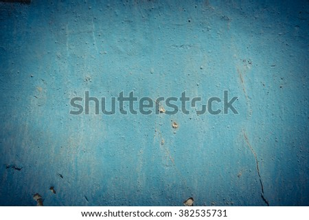 Close-up view a weathered, rough and dirty concrete wall with cracked stucco layer. Rustic blue grunge material from old wall seamless texture in an ancient town of Vietnam. - stock photo