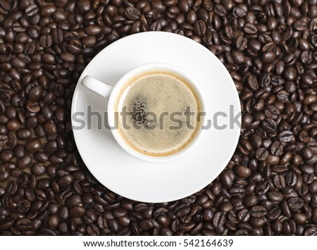 Close-up view from above of a cup of coffee over coffee beans. Texture.