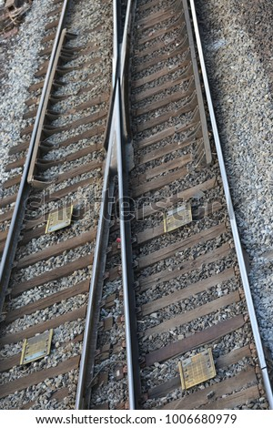 Close up view from above of a pair of rails. Leading parallel steel rails with regular crossbars. Pattern composed by the different lines and texture underlined by the gravel. Abstract geometric view.