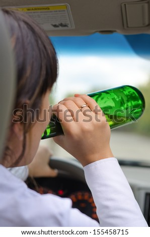 Close up view from behind of an alcoholic woman driver drinking while driving on a road with the bottle of alcohol upended to her lips - stock photo