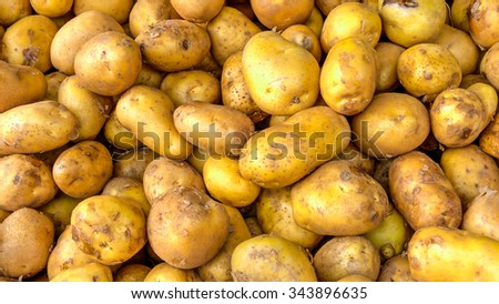Close-up view heap of fresh and organic raw ripe potatoes tubers on display at Vegetable Stall at Local Market in Little India, Singapore. Natural food ingredient background and pattern texture - stock photo