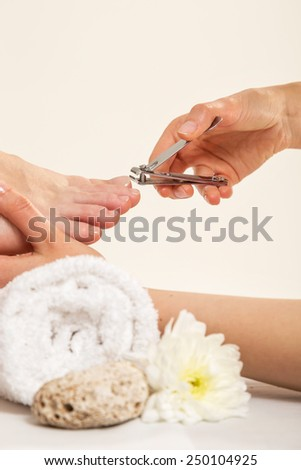 Close up View Of A Beautician's Hand Cutting Client's Toenails - stock photo