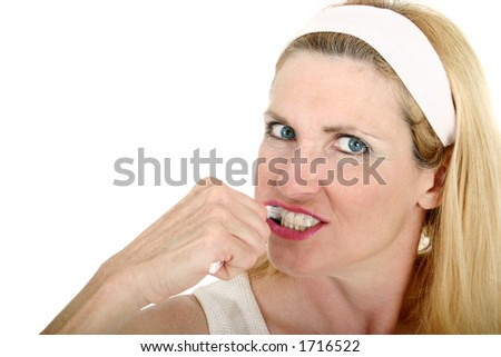 Close-up view of a beautiful middle-aged woman brusing her teeth.  Shot isolated on white background. - stock photo