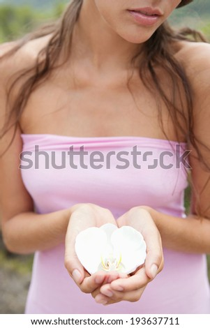 Close up view of a beautiful young woman hands together holding an exotic white orchid flower while visiting a tropical lush forest spa on a summer holiday. Spring outdoors and healthy lifestyle.