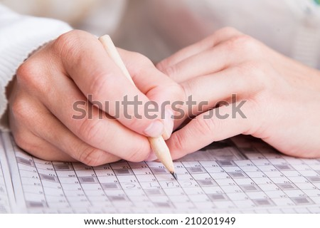 Close up view of a blank crossword puzzle grid with black and white squares and a pencil - stock photo