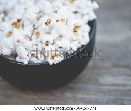 Close-up view of a bowl of white popcorn on rustic, wooden table, shallow DOF - stock photo
