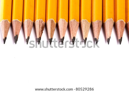 Close up view of a bunch of yellow pencils isolated on a white background. - stock photo